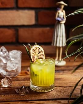Een cocktail van het vooraanzichtfruit met ijsblokjes op het bruine houten fruit van de bureaucocktail drinkt sap