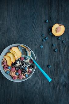 Een cocktail van verse bessen, chiazaden, fruit en amandelen. set van bessen, frambozen, perzik, bosbessen. gezond ontbijt. gezond evenwichtsvoedsel.