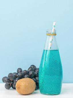 Een cocktailfles met basilicumzaden met een cocktailbuis op een blauwe oppervlakte