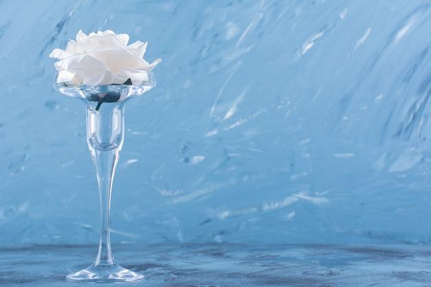 Een cocktailglas met witte roze bloem op blauw.