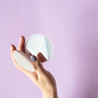 Een compacte, compacte spiegel in de handen van vrouwen