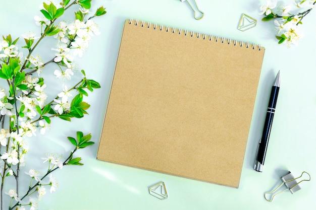 Een compositie met een mock-up van een blanco pagina van een kraftpapier notitieboek, pen en kantoorclips met een bloeiende kersentak met bloemen op een pastelblauwe achtergrond. bovenaanzicht.