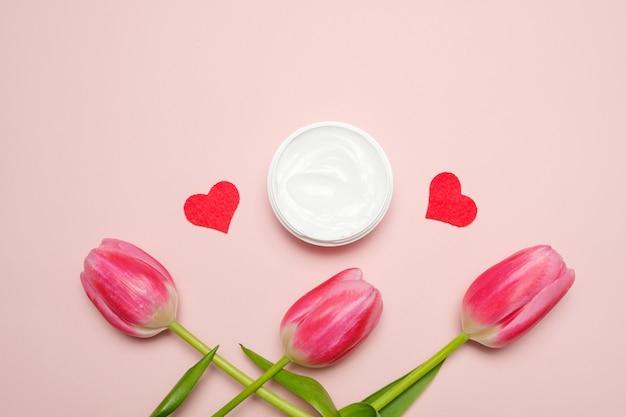 Een compositie met tulpen en een potje handcrème op een roze achtergrond.