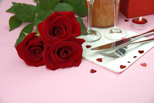 Een compositie van een mooi boeket rozen, glazen en een fles champagne creëert een romantische kaart of poster. het concept van valentijnsdag, moederdag, 8 maart.