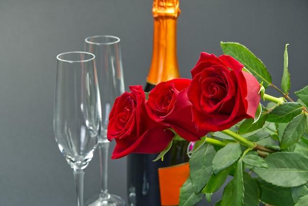 Een compositie van een mooi boeket rozen, glazen en een fles champagne zorgt voor een romantische kaart. het concept van valentijnsdag, moederdag, 8 maart.
