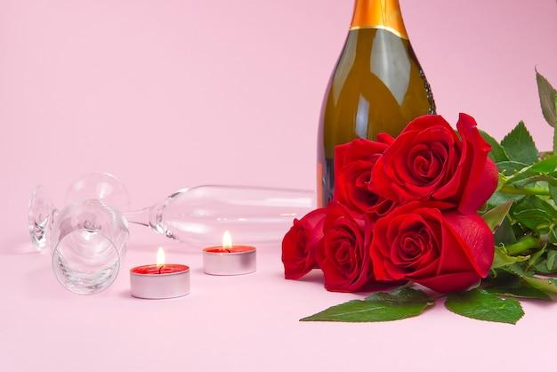 Een compositie van een mooi boeket rozen, kaarsen, glazen en een fles champagne zorgt voor een romantische kaart. het concept van valentijnsdag, moederdag, 8 maart.