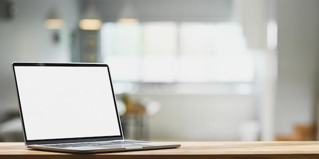 Een computerlaptop zet op een houten toonbank in de woonkamer