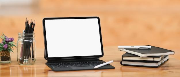 Een computertablet met een wit leeg scherm en diverse apparatuur worden op een houten tafel gezet.
