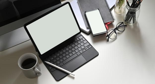 Een computertablet met een wit leeg scherm zet op een bureau, omringd door verschillende apparatuur.