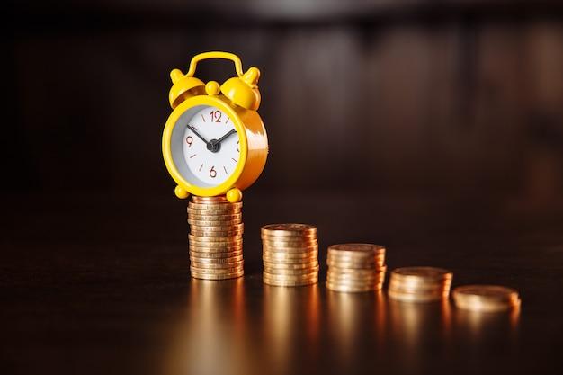 Een concept over de relatie tussen tijd en geld. een wekker en een stapel munten.