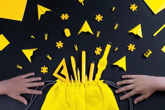 Een concept over het onderwerp terug naar school met handen. de gele briefpapier van de student op een zwarte achtergrond.