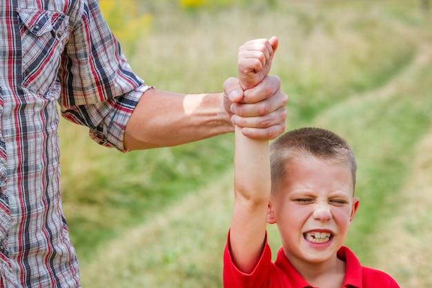 Een concept van handen van ouder en schreeuwend kind in pirodev park