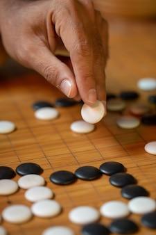 Een concurrent plaatst een marmeren stuk op een bordspel go.
