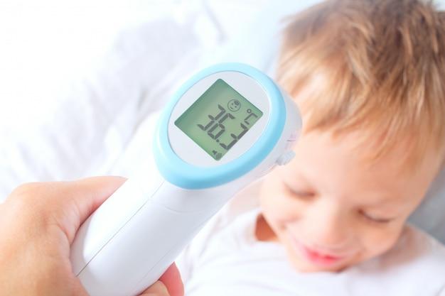 Een contactloze digitale infraroodthermometer registreerde de normale lichaamstemperatuur van een kind. de jongen is aan het herstellen van een ziekte. succesvolle preventie van verkoudheid en griep bij kinderen.