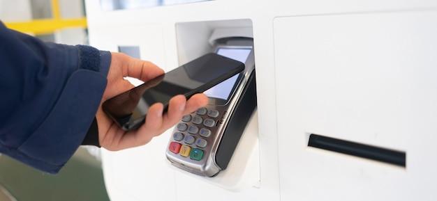 Een contante betaling met telefoon naar pos-terminal met nfc-technologie