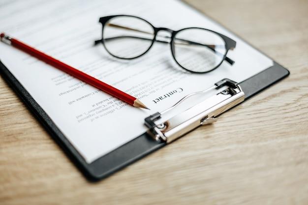 Een contract op een houten werktafel met glazen en een rood potlood. de documenten zijn klaar voor ondertekening. bedrijfsconcept. samenwerkingsovereenkomst.