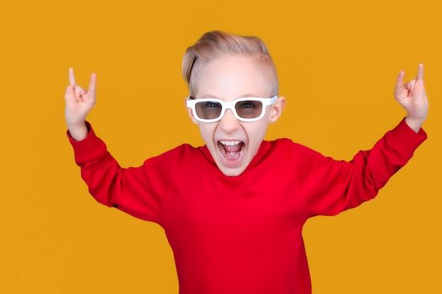 Een cool en vrolijk kind in rode kleren en een bril toont handgebaren op een gele achtergrond