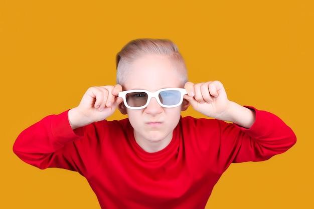 Een cool kind in een rood jasje houdt zijn handen tegen zijn bril op een gele pagina