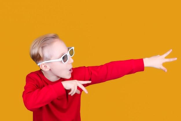 Een cool kind op een gele achtergrond en in een 3d-bril voor kinderen wijst met zijn handen de richting naar de zijkant