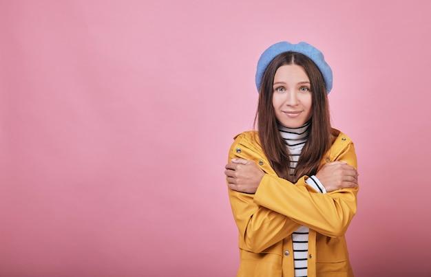 Een cool meisje met groene ogen en een mooi gezicht in een trillende gele regenjas
