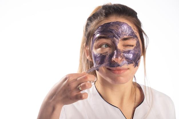 Een cosmetisch masker om de poriën te reinigen wordt aangebracht op het gezicht van een jonge vrouw