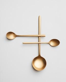 Een creatieve compositie gemaakt van verschillende gouden lepels op een grijze achtergrond. bovenaanzicht