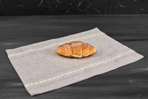 Een croissant op een theedoek.
