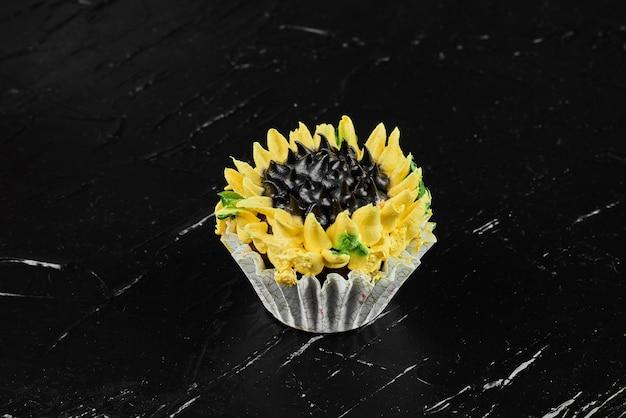 Een cupcake vorm zonnebloem op zwarte ondergrond.