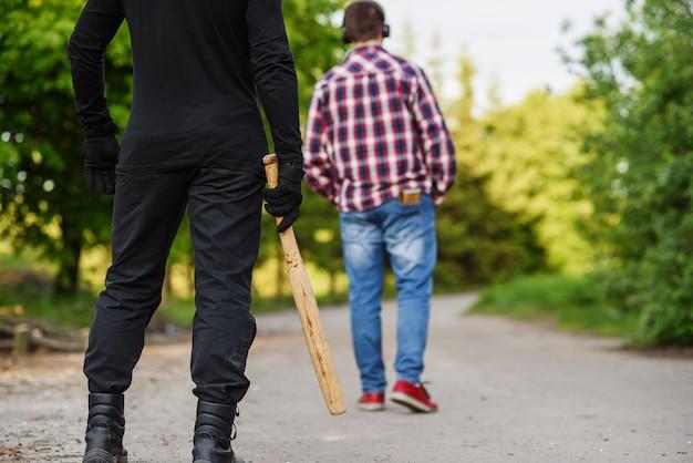 Een dader in zwarte kleding met een honkbalknuppel in zijn handen valt een man aan. zakkenrollen op straat overdag.