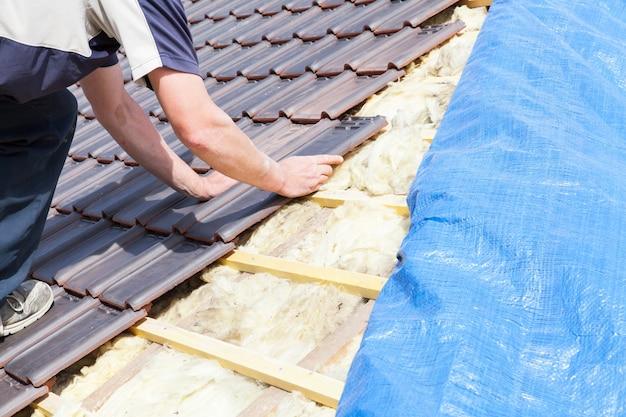 Een dakdekker die tegel op het dak legt