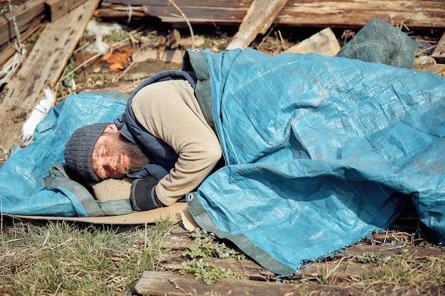 Een dakloze man bij de ruïnes slaapt op kartonnen dozen en helpt arme en hongerige mensen tijdens de epidemie