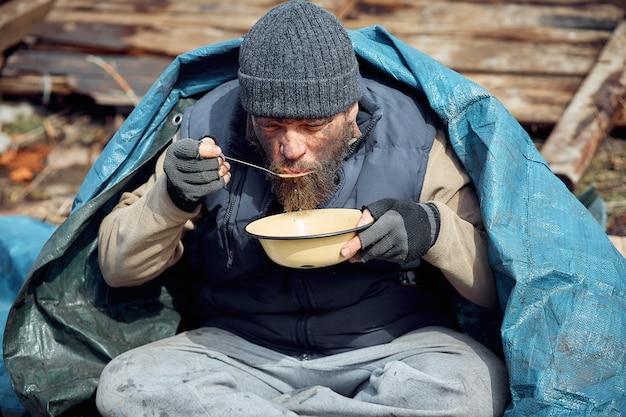 Een dakloze man eet soep van een bord bij de ruïnes en helpt arme en hongerige mensen tijdens de epidemie