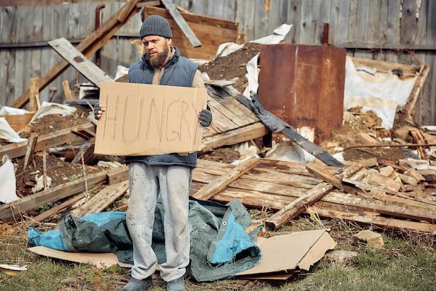 Een dakloze man in de buurt van de ruïnes met een bord met honger, die arme en hongerige mensen helpt tijdens de epidemie