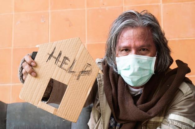 Een dakloze man met een bord dat om hulp vraagt