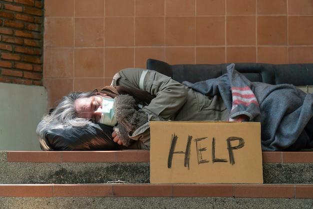 Een dakloze man slaapt aan de kant van de weg.