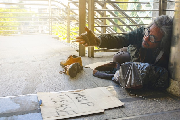 Een dakloze man zit op loopbrug in de stad. hij is het woord