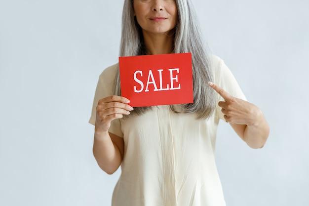 Een dame van middelbare leeftijd met lang grijs haar houdt een rood verkoopbord vast dat met de vinger wijst op een lichte achtergrond in de studioclose-up