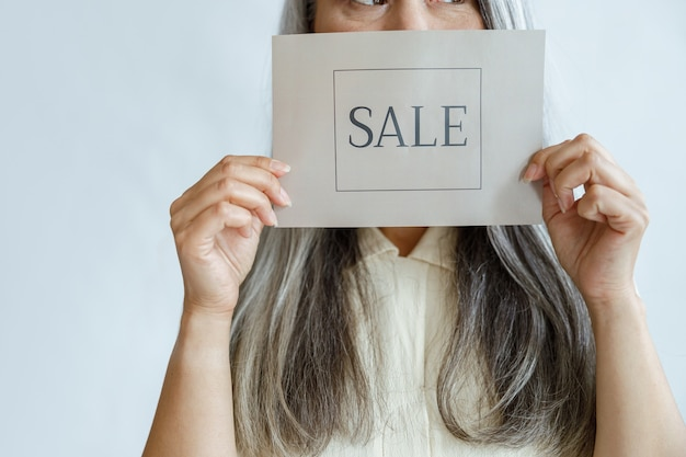 Een dame van middelbare leeftijd met los grijs haar houdt een verkoopbordje in de buurt van een gezicht dat in de studio staat