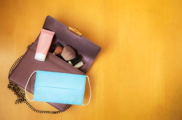 Een damestas met lippenstift, oogschaduw, zonnebrandcrème, handdesinfecterend middel en gezichtsmasker om coronavirusinfectie te voorkomen