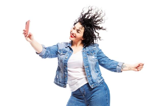 Een dansend lachend meisje kijkt naar de telefoon en neemt een selfie