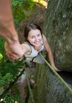 Een dappere mannelijke rockclimber houdt een onverschrokken klimmer met de hand op een rotsachtige muur