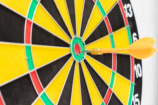 Een dartboard met een pijl in bullseye dichte omhooggaand, doelstellingen en het richten concept