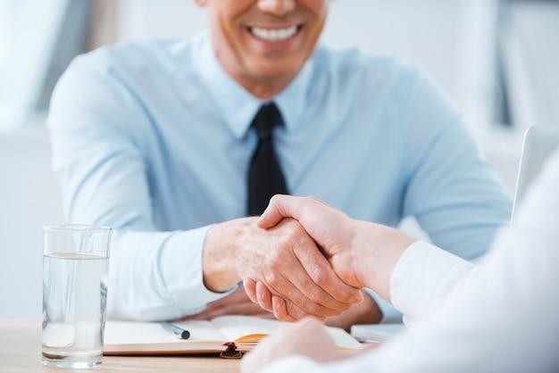 Een deal sluiten. close-up van twee zakenmensen die handen schudden terwijl ze op de werkplek zitten