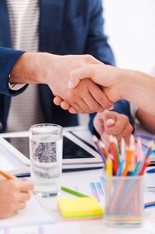 Een deal sluiten. close-up van zakenmensen in slimme vrijetijdskleding die handen schudden terwijl ze samen aan tafel zitten