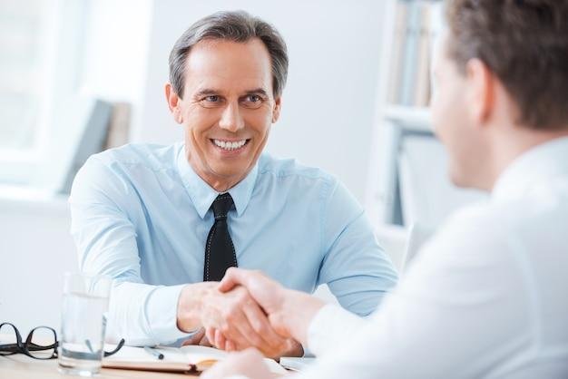 Een deal sluiten. twee zakenmensen die handen schudden terwijl ze op de werkplek zitten working