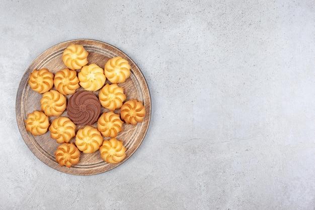Een decoratief arrangement van hartige koekjes op een houten bord op marmeren achtergrond.