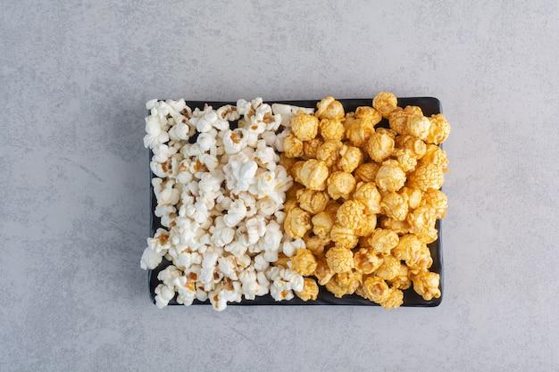 Een decoratief stuk bovenop schalen met gecoate popcornsnoepjes op marmer.
