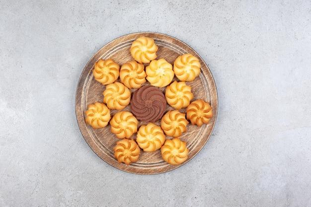 Een decoratieve regeling van cookies op een houten bord op marmeren achtergrond. hoge kwaliteit foto