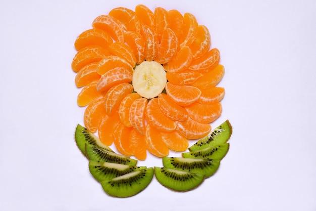 Een decoratieve vorm in de vorm van een bloem op een witte achtergrond is gemaakt van plakjes mandarijn en kiwi