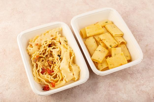 Een deeg maaltijd van bovenaanzicht en italiaanse pasta met tomaten en vlees in witte kommen op roze